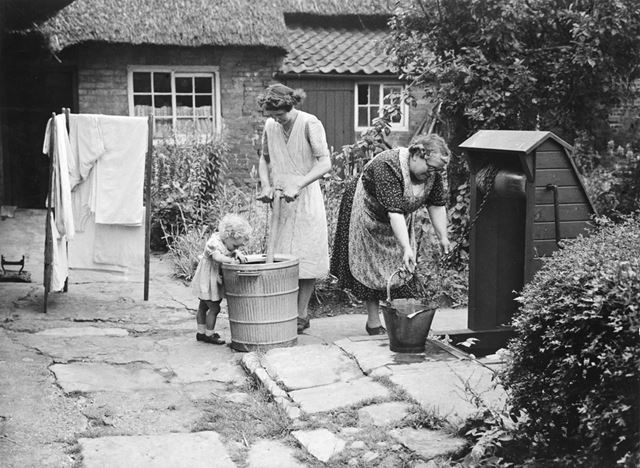 A family in the garden of a timber-framed thatched cottage, Clifton Village, 1948