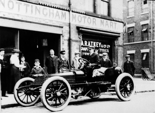 A 50 HP racing Wolsley motor car and spectators outside A R Atkey's Garage